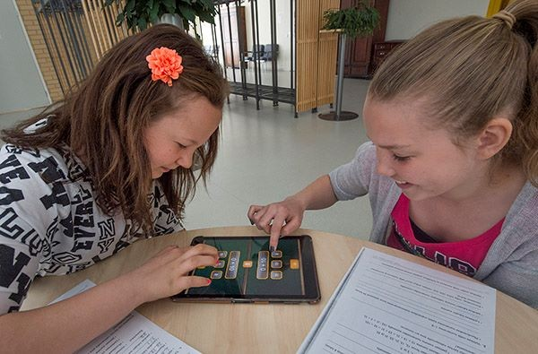 Johanna Kuosa ja Julia Humalamäki pelaavat Math Fight -matematiikkapeliä koulun uudella iPadilla.