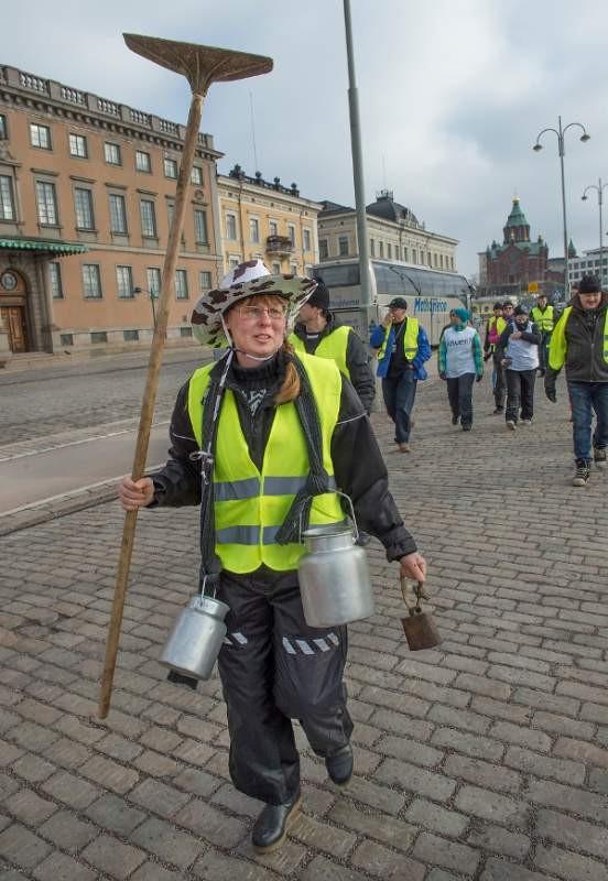 Somerolainen Kaija Pirttilä otti mielenositukseen mukaan maitotilaan viittaavaa rekvisiittaa.