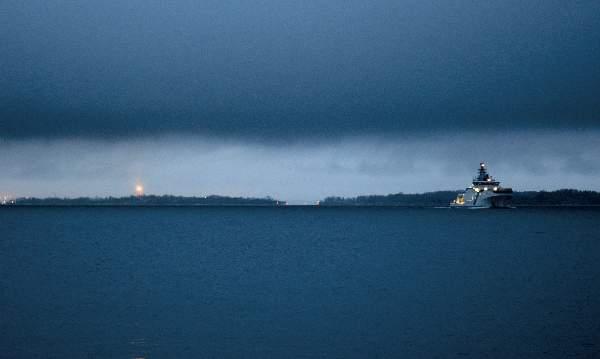 Merivartioston Turva-ulkovartioalus lipuu pimeälle merelle. Taustalla vilkkuu Suomenlinnan majakka.