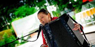 Anna Schukov laulaa ja laulattaa Vuohensaaressa yhteislauluja maanantaina. Kuva vuodelta 2011.
