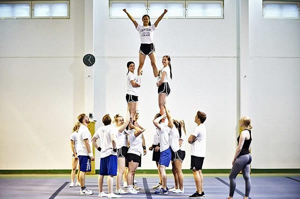Kolmen kerroksen väkeä. Pyramidit ovat cheerleadingin näyttävintä antia. Big A eli iso A koostuu kolmesta kerroksesta. Aikuisten sekajoukkueen Raptorsin jäsenten mukaan kilpacheerleading on jotain muuta kuin tanssimista stadioneilla matsien aikana. Vauhdikas laji koostuu hypyistä ja akrobatiasta sekä ryhmien tekemistä tempuista ja pyramideista. Kilpailuissa suoritus kestää noin 2,5 minuuttia. Kuva: Ari-Matti Ruuska, Turun Sanomat.