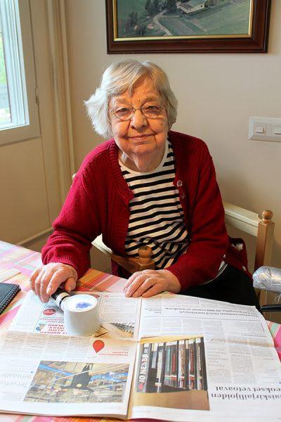 Apuvälineet auttavat kotona. Laitilalainen Aune Alkila, 92, esittelee apuvälinettä, jonka avulla voi omatoimisestikin selailla sanomalehteä. Valollinen suurennuslasi on usein käytössä. Alkila kertoo pärjäävänsä kotona hyvin nykyisillä tukitoimilla. Arkipäivisin kotihoito käy hänen apunaan kolmasti päivässä ja ruokapalvelu kuljettaa lämpimän aterian kotiin saakka. Keskiviikkoisin on suihkupäivä ja lapset auttavat erilaisissa askareissa, kuten siivoamisessa ja kauppakäynneissä. Kerran kuukaudessa siivooja siivoaa kodin perusteellisemmin. Kuva: Solina Saarikoski, Laitilan Sanomat.